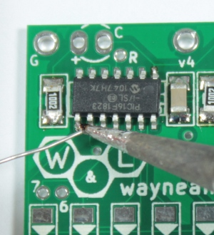 Tack the chip in place by soldering a pin in the opposite corner